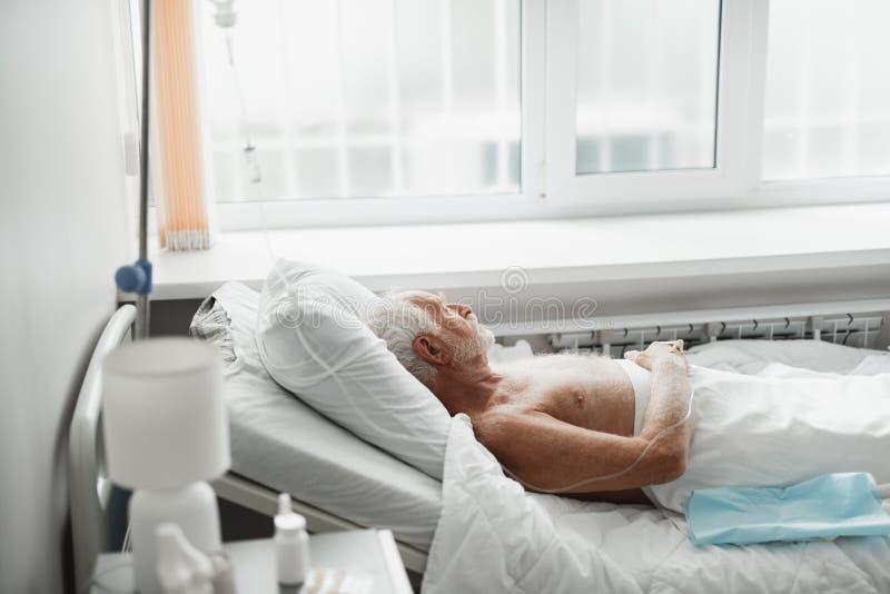 Ancião que encontra-se na cama e que recebe o tratamento intravenoso fotos de stock royalty free