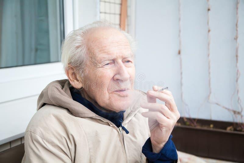 Ancião que expira o fumo fotos de stock