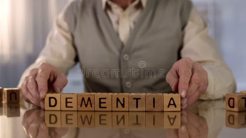 Ancião que faz a demência de cubos de madeira na tabela, doença da palavra de cérebro, saúde imagem de stock