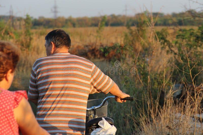 Ancião que monta uma bicicleta na estrada de terra do país para o céu ensolarado do por do sol Copie o espaço para o texto foto de stock
