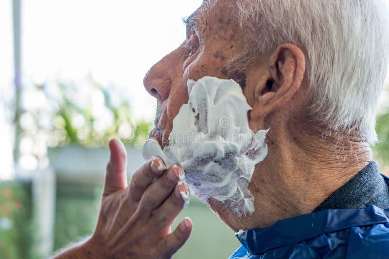 Ancião que obtém sua barba barbeada pelo homem especializado novo em casa fotos de stock royalty free