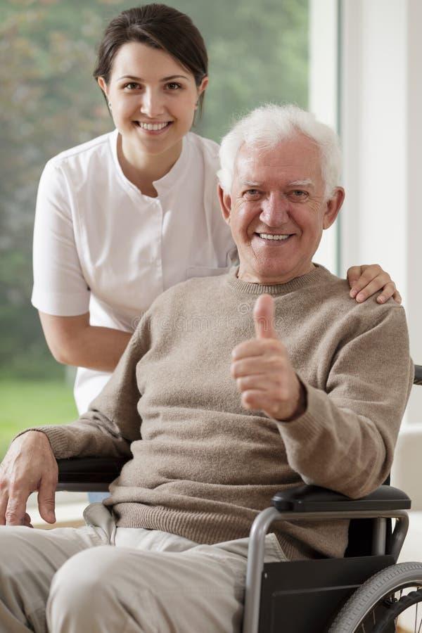 Ancião que senta-se na cadeira de rodas fotografia de stock royalty free