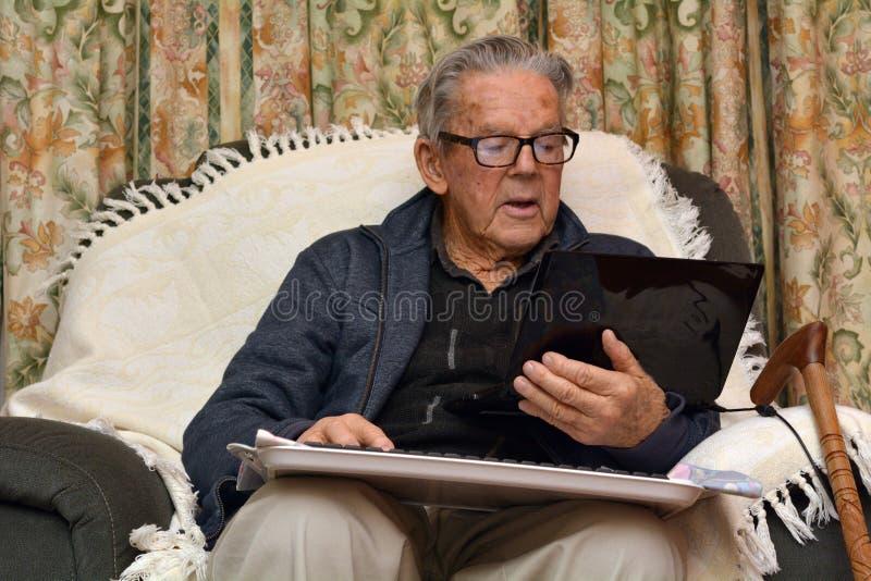 Ancião que trabalha com laptop em casa foto de stock