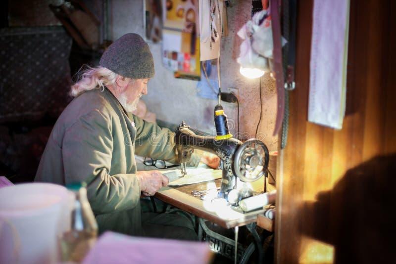 Ancião que trabalha na máquina de costura fotos de stock royalty free