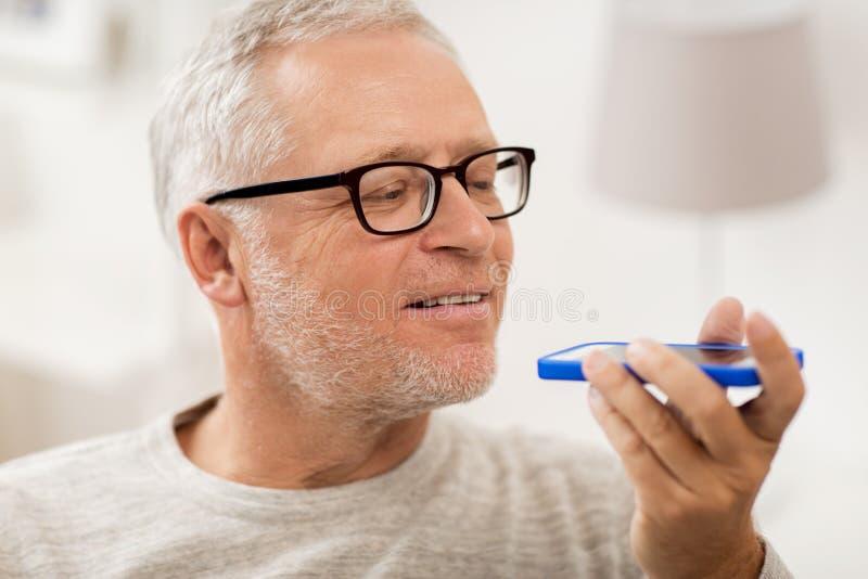 Ancião que usa o registrador do comando da voz no smartphone fotos de stock
