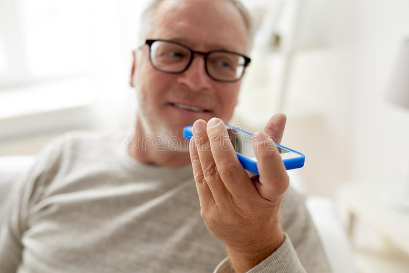Ancião que usa o registrador do comando da voz no smartphone imagens de stock