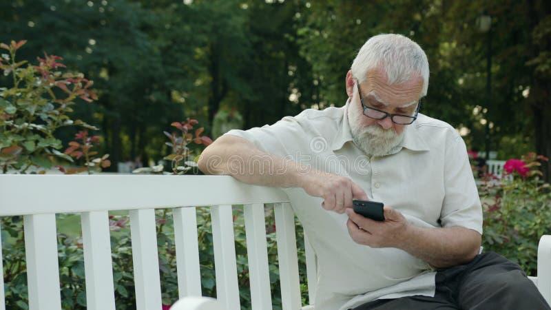 Ancião que usa um telefone fora foto de stock