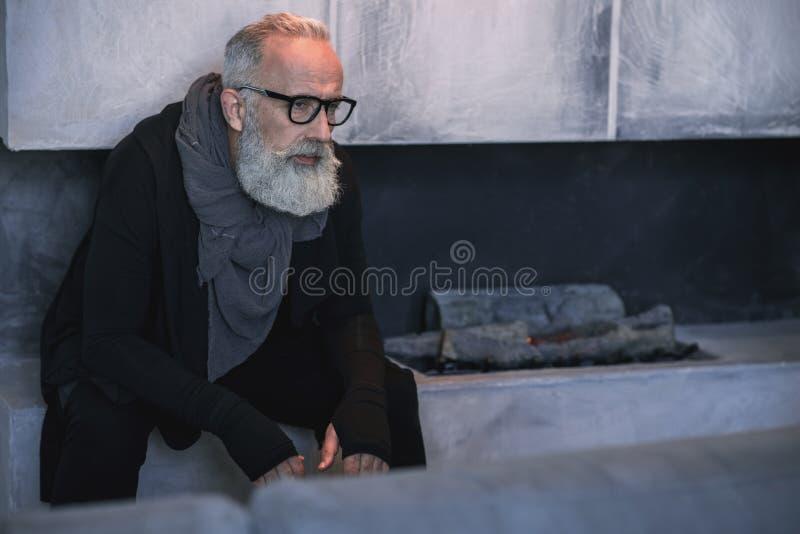 Ancião sério que senta-se em casa foto de stock royalty free