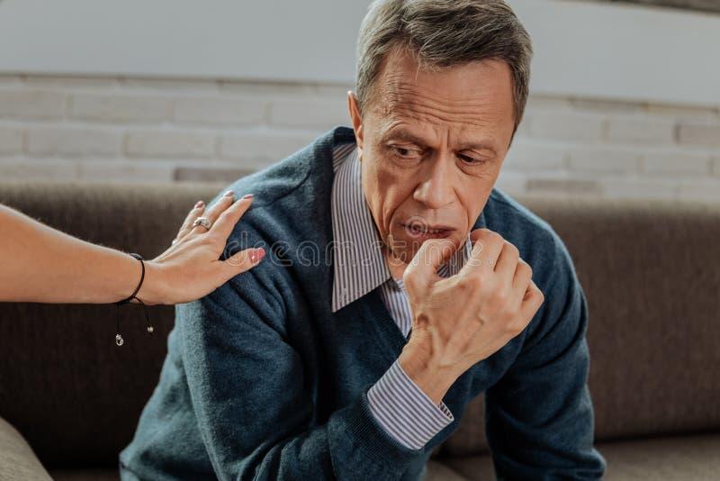 Ancião triste e cansado com o cabelo curto que é deprimido durante a sessão imagens de stock royalty free