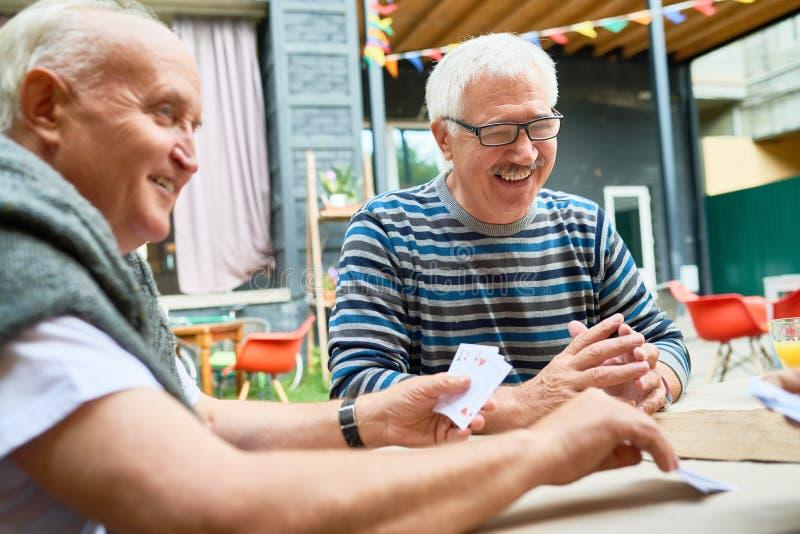 Anciões felizes que jogam o jogo de cartas imagem de stock