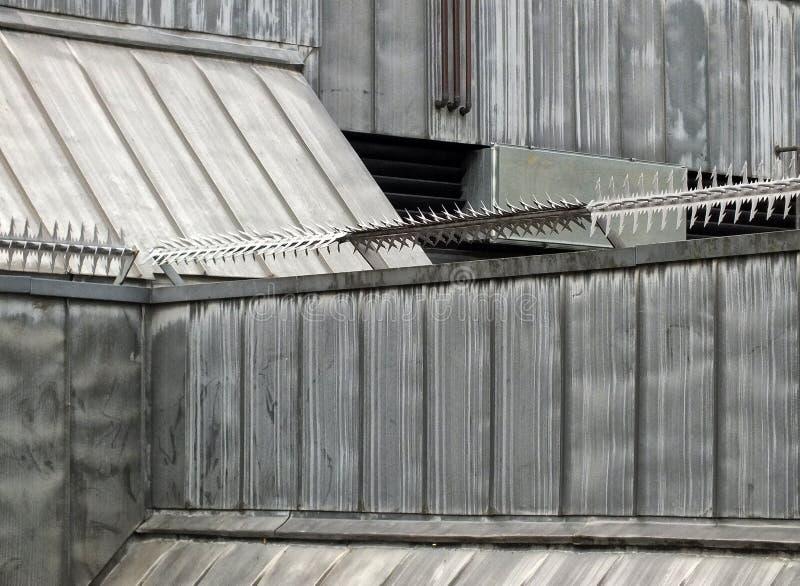 Anci wspinaczki ochrony rolowniki z barbed kolcami na dachu wysokie bezpieczeństwo budynek z popielatymi połogimi powierzchniami  zdjęcie stock
