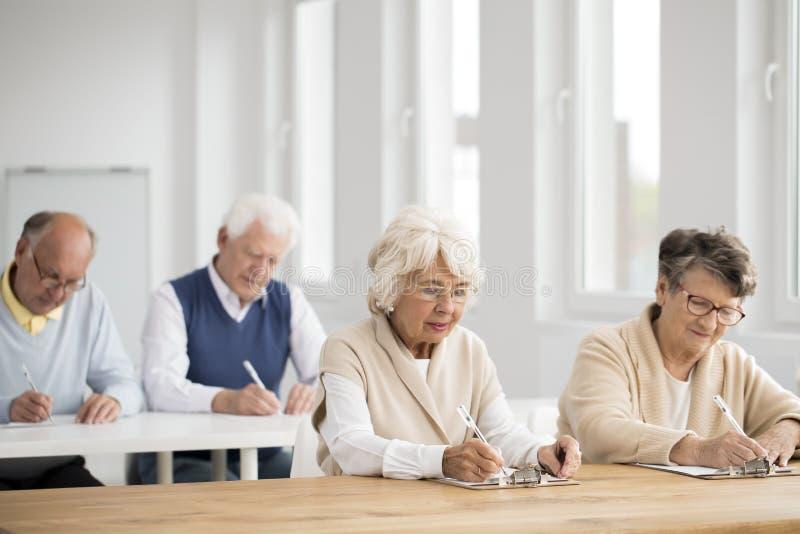 Ancianos durante examen de las TIC imagenes de archivo