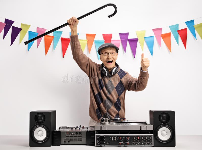 Ancianos extáticos DJ con un bastón que hace un pulgar encima del gesto fotos de archivo libres de regalías