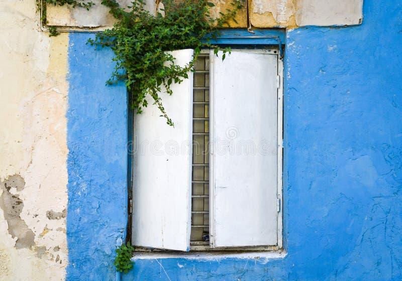 Ancien rostigt metallfönster på ett gammalt hus med målade blåa väggar royaltyfri fotografi