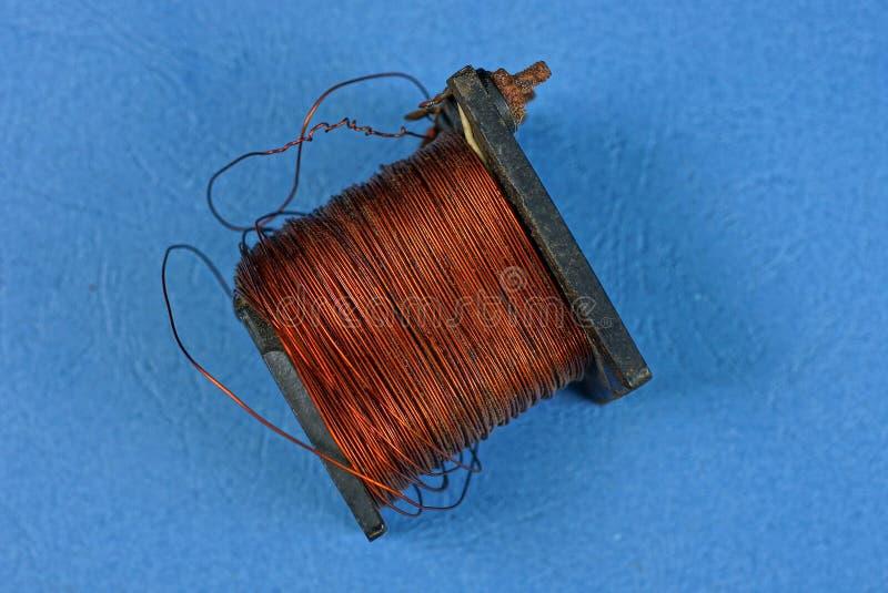 Ancienne bobine noire avec fil de cuivre rouge photographie stock libre de droits