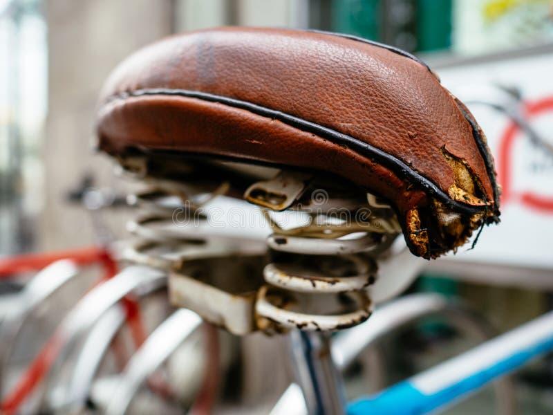 Ancienne selle déchirée du vélo. Selle en cuir de bicyclette image stock