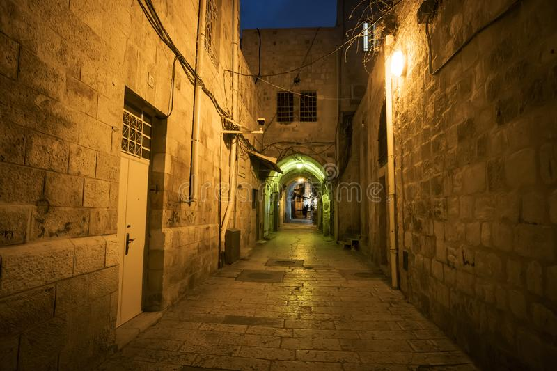 Ancient alley in Jewish Quarter at night time, the old city Jerusalem. Mystical atmosphere of deserted road leading to an old city royalty free stock photography