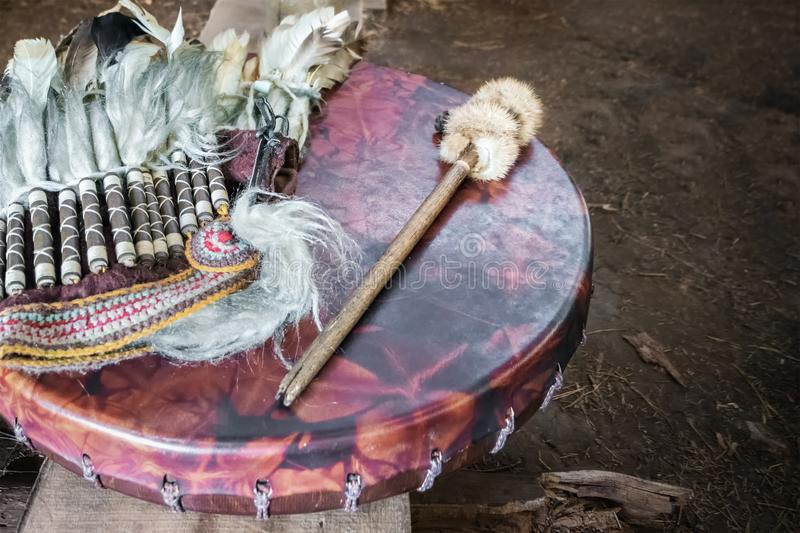 Ancient amerindian tambourine, drum drumstick replica and a feather headdress. royalty free stock images