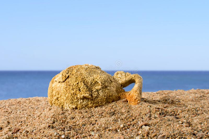 Ancient amphora lying on the sand against the blue sky, found in Greece stock photo