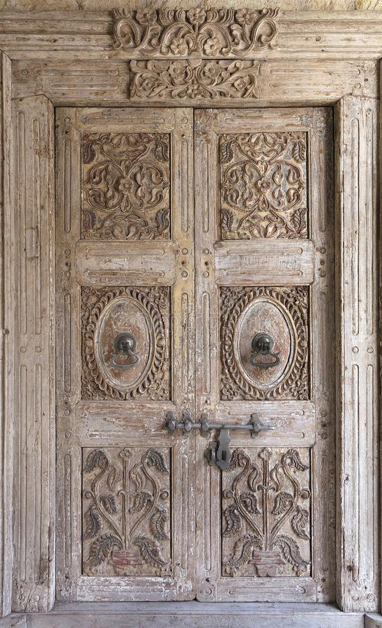 Ancient antique wooden doors with metal handles and a lock in the middle stock photography