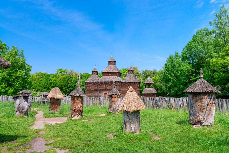 Ancient apiary in wooden bee hive. With wooden buildings on background stock photography