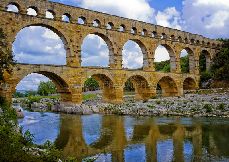 Ancient Aqueduct, Provence France. Reflected in the golden light of the afternoon, the Pont du Gard, in Provence, France, over the Gardon River, is an 160 foot