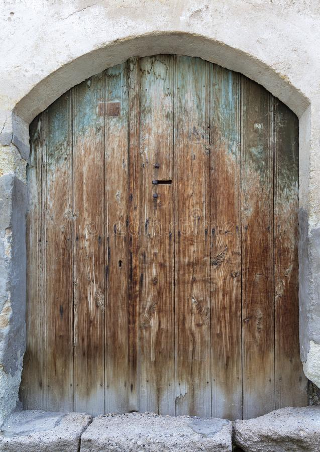Ancient arched antique wooden doors with a metal lock in the middle royalty free stock photography