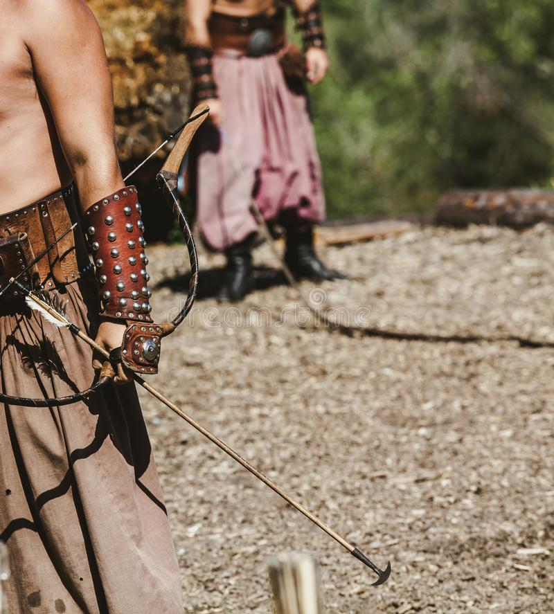 Ancient warrior holds bow and arrow in his hands royalty free stock photography