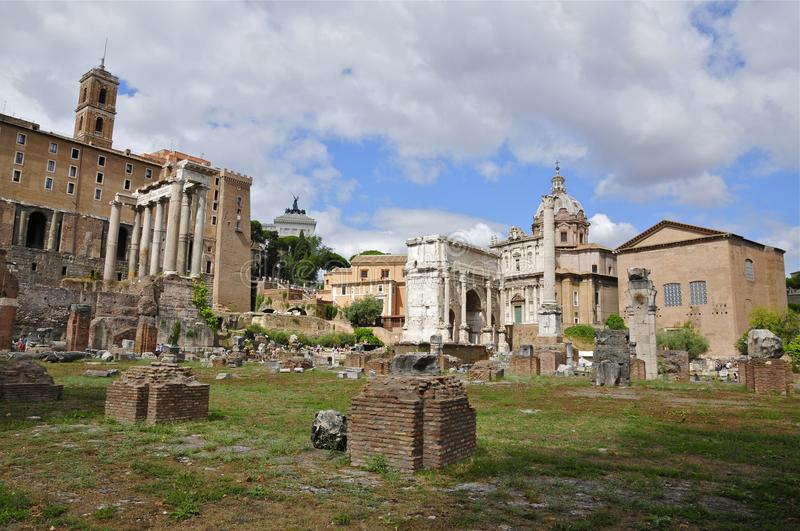 Roman Forum North. Ancient architectural fragments: Temple of Saturn and triumphal arch of Septimius Severus stock photos