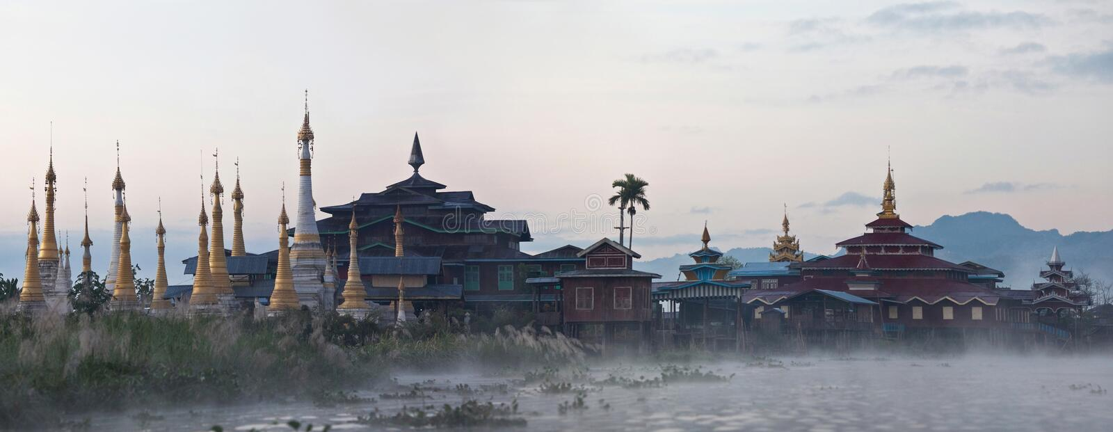 Ancient Aung Mingalar pagoda on Inle lake, Myanmar. Panorama of ancient Aung Mingalar pagoda and monastery over thick mist on Inle lake, Shan state, Myanmar stock image