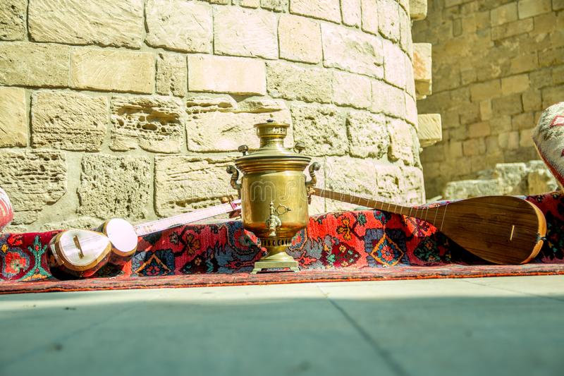 Ancient azerbaijani musical instruments tar and saz with old vintage azeri tea pot for boiling water stock photo