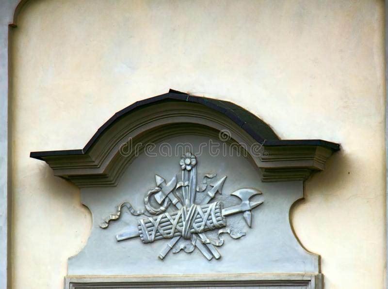 Ancient bas-reliefs on the Windows and walls of historical buildings. Architectural design elements from the past. Warsawa. Shield, ax and spear on the crown stock image