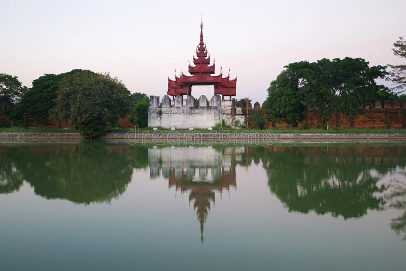 Ancient bastion of the old city with reflection in gray twilight. Mandalay, Burma. Myanmar royalty free stock images