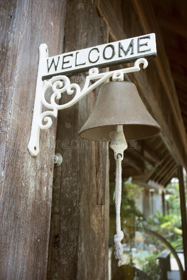 Ancient bell hanging on a metal bar of welcome label with blurred background,selective focus,filtered image,vintage tone process.  royalty free stock photos