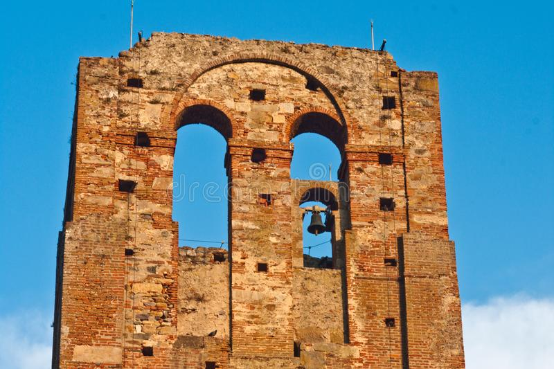 Ancient brick tower with arches and bells stock image