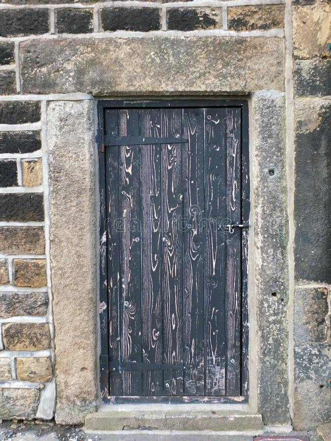 Ancient black wooden door with old faded peeling paint in a heavy stone frame with a closed bolt and metal hinges. Ancient black wooden door with old faded stock photography