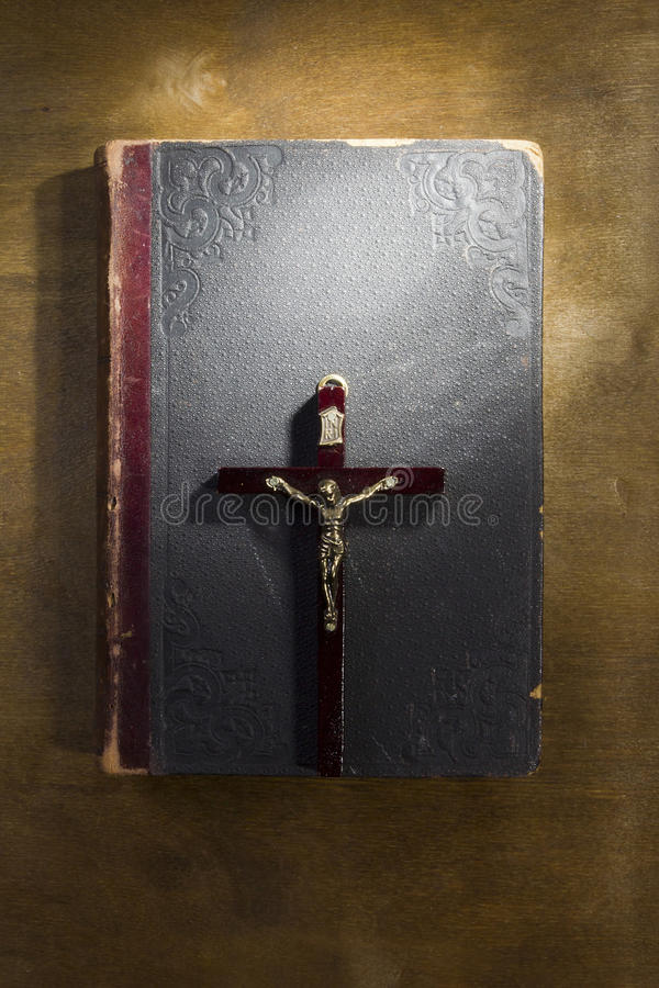 Ancient book and crucifix. On a wooden table stock photography