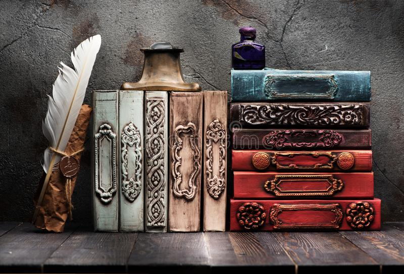Ancient books, manuscript with a wax seal on the shelf, ink in a bottle and bronze inkwell stock photo