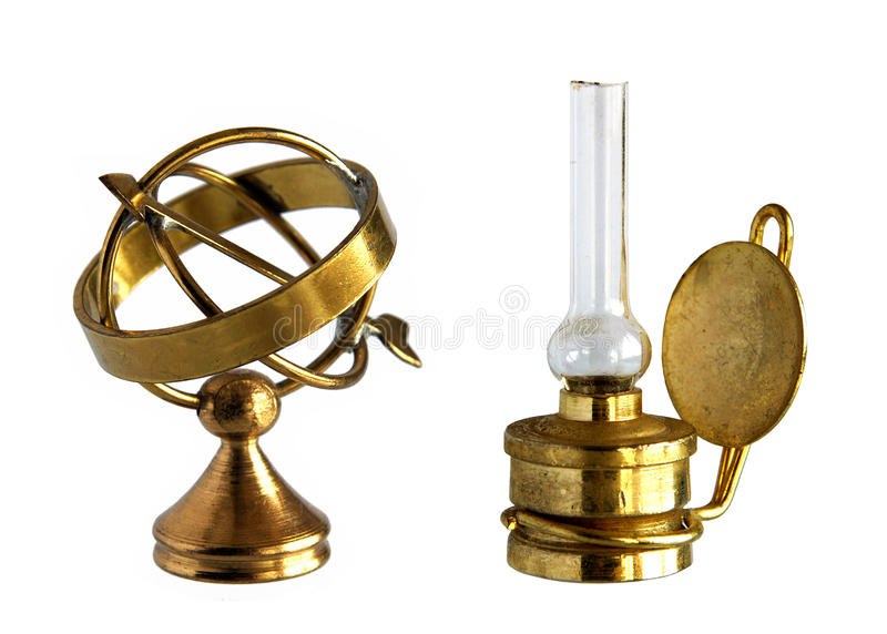 Ancient brass astrolabe and kerosene lamp royalty free stock photography