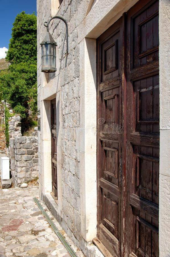 Ancient brick building in the fortress old bar, Montenegro. Antique wooden door and old lantern. stock images