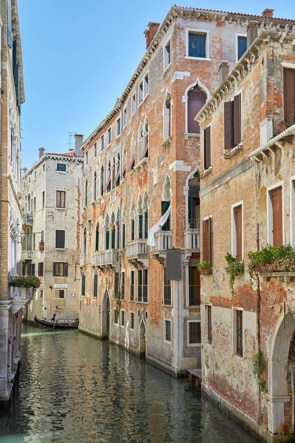 Ancient brick buildings and canal with gondola passing in a summer day in Venice, Italy stock photos