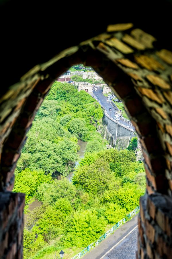 River and castle bridge. View from loophole of tower. Ancient bridge of Kamianets-Podilskyi Castle in Ukraine. Top down view from defense tower of fortress royalty free stock photo