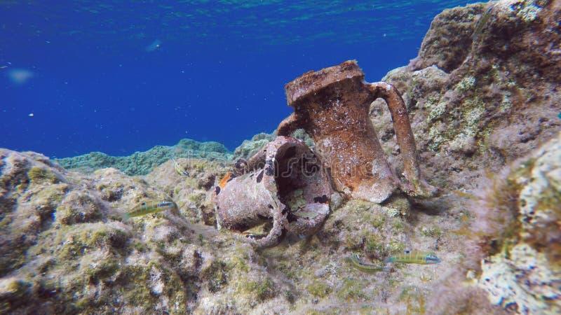 Ancient Greek Amphorae Relics Underwater. Ancient Broken Greek Clay Amphorae Relics On Rocky Seabed, With A Deep Blue Sea Horizon. Underwater Aegean Sea, Kythira stock photography