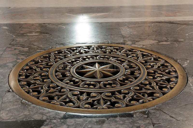 Ancient bronze lattice on the vent hole in the floor. Ancient bronze lattice on the vent hole in the marble floor royalty free stock images