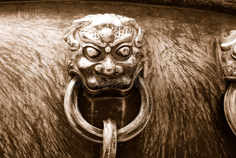 Ancient bronze lions as a handle of vat - in sepia royalty free stock photography