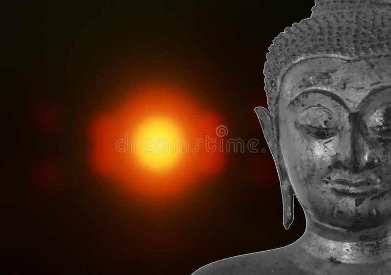 ancient Buddha image on blurry candle light in dark royalty free stock image