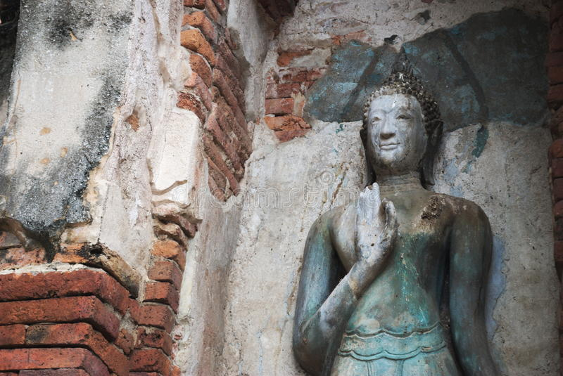 Ancient Buddha Statue beside the wall. Ancient Buddha Statue beside the temple wall stock photography