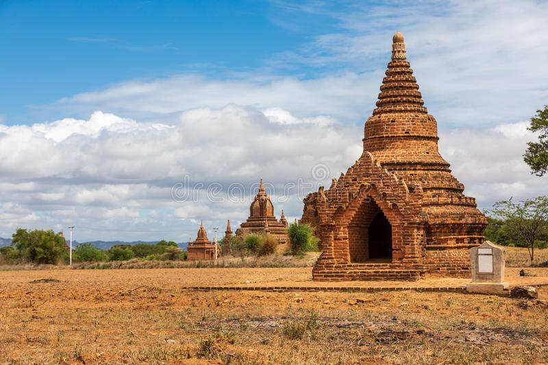 Ancient Buddhist pagoda temple in Mandalay in Burma, Myanmar. Lacality: Taungbi in the city of Nyaung-U in the Mandalay region. On a field with clear sky with stock images