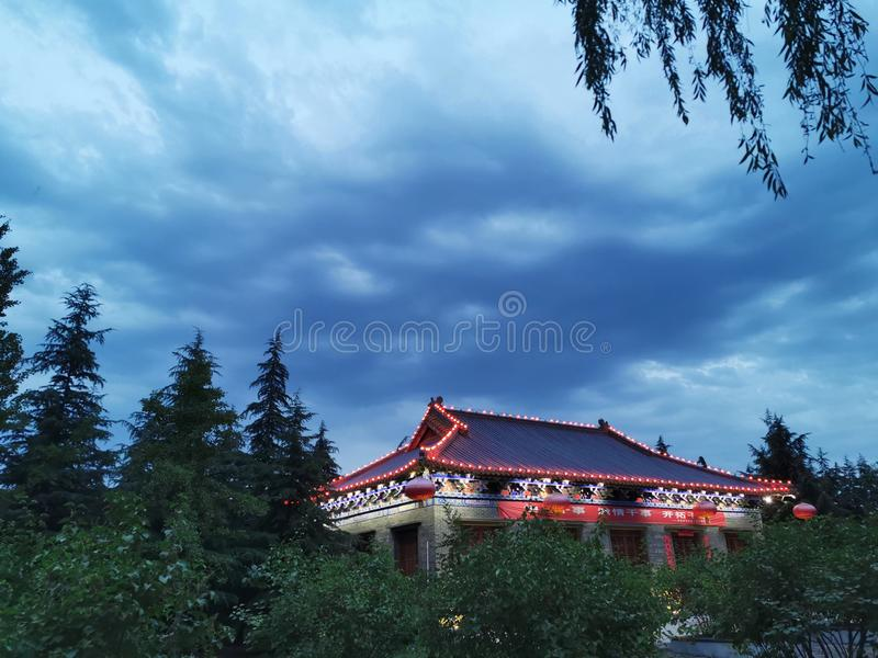 In the ancient building under the night scene, the willow branches form a beautiful picture. royalty free stock image