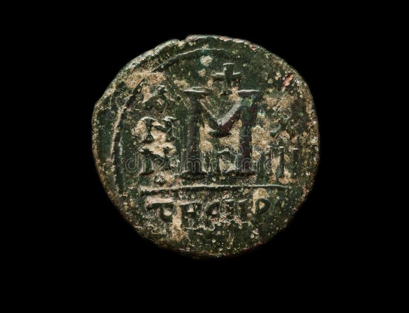 Ancient Byzantine copper coin with big letter M stock images
